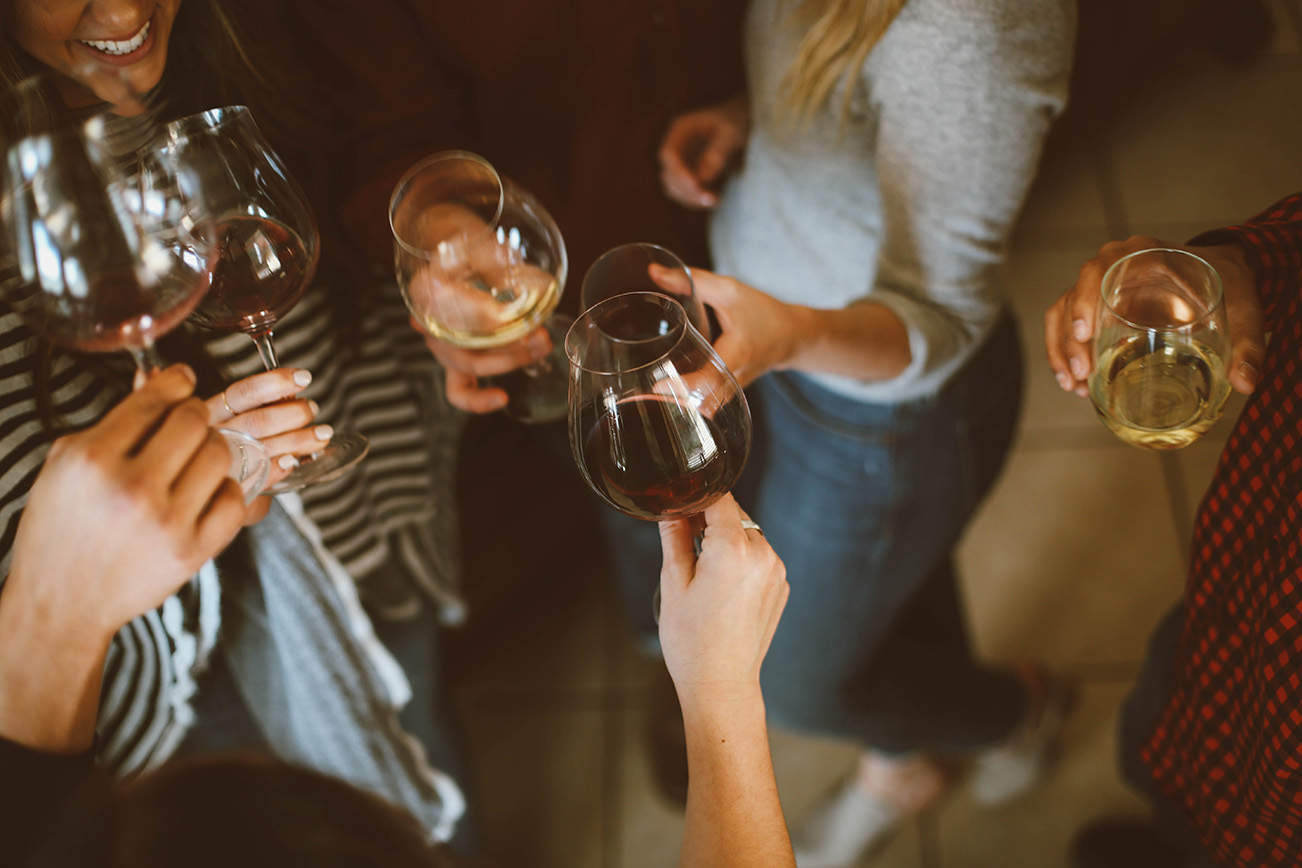 groupe de personne avec un verre de vin en train de trainqué